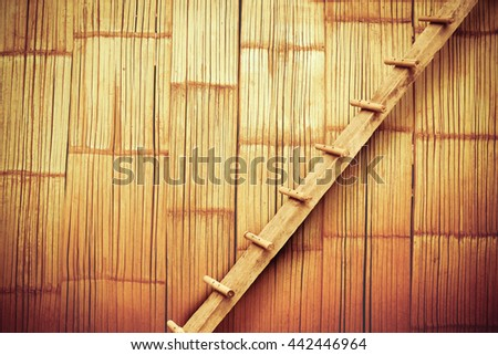 wooden ladder with old bamboo wall background - stock photo