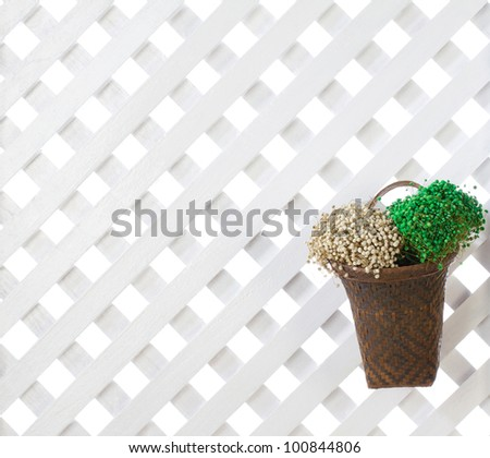 Wooden lattice background with dried flowers in bamboo basket