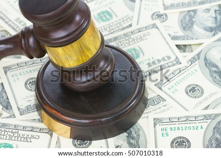 Wooden Law Gavel on Dollar Money background close up