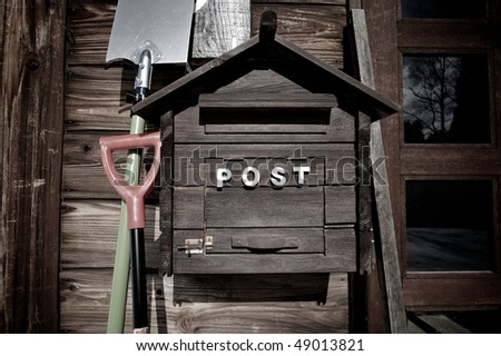 Wooden letterbox with garden tools against wall - stock photo