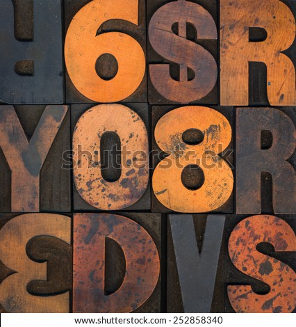 Wooden letterpress letters and numbers stained with printing ink. - stock photo