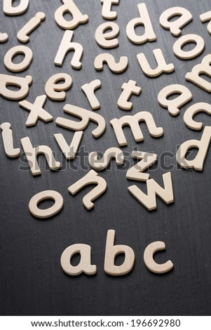 Wooden letters arranged to spell abc for the alphabet on a blackboard - stock photo