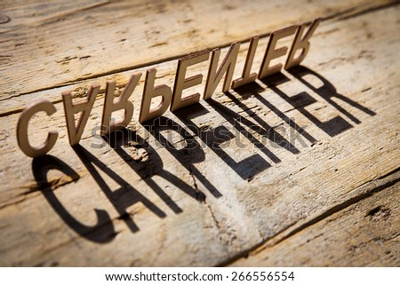 wooden letters on old aged wooden table build the shadow word carpenter, vintage style - stock photo