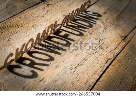 wooden letters on old aged wooden table build the shadow word crowdfunding, vintage style - stock photo