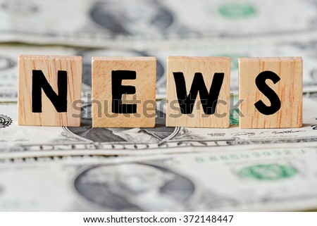 Wooden letters spelling news on money background
