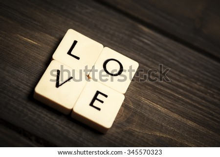 Wooden letters spelling the word LOVE. On a textured wooden background with copy space