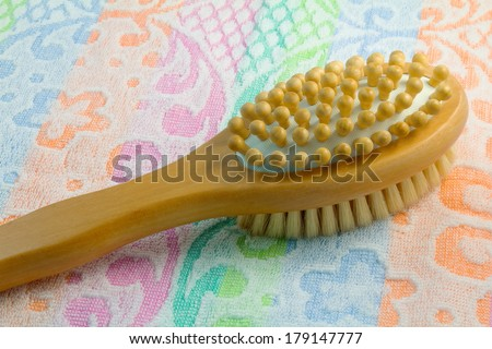 Wooden light brown brush with the long handle for body massage.