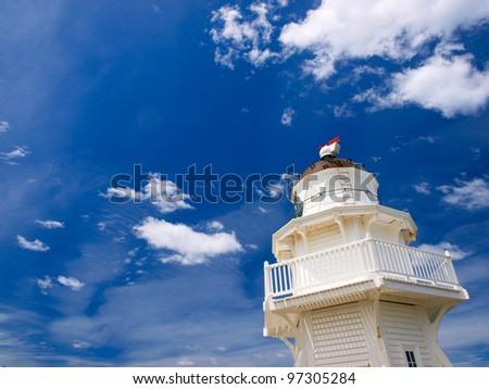 Wooden lighthouse against sunny summer sky - stock photo