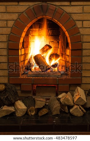 wooden logs and fire in fireplace in country cottage