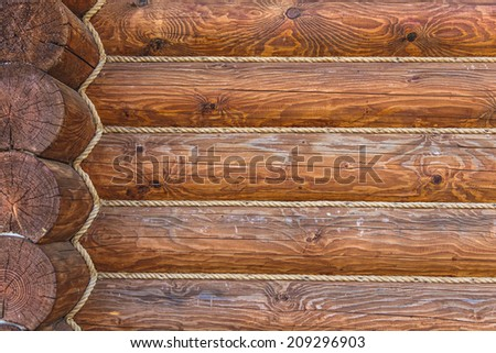 Wooden logs wall with rope of rural house background