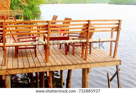 Wooden Lounge Chairs And Furniture At Timber Patio Deck Along The River