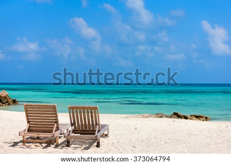 Wooden lounge chairs on a beautiful tropical beach at Maldives - stock photo