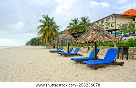 Wooden lounge / deck chairs and umbrella on paradise beach looking out to ocean, blue sky - stock photo