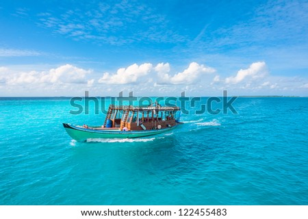 Wooden Maldivian traditional dhoni boat on a sunny day and turquoise ocean water