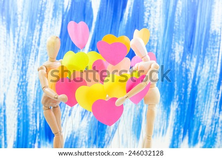 Wooden, male, female, are embracing the heart of all colors, background colors, Blue - stock photo
