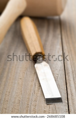 Wooden mallet and chisel on wooden workbench table, selective focus on chisel blade - stock photo