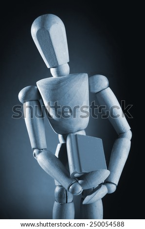 Wooden man holding book in black and white. - stock photo