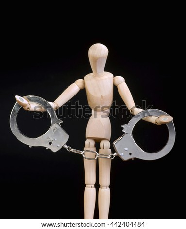 Wooden manikin arrested in handcuffs. - stock photo