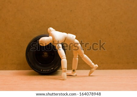 wooden manikin looking into camera lens.