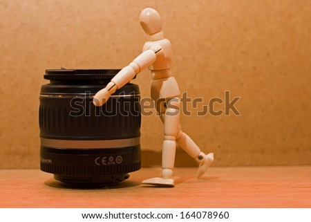 wooden manikin looking into camera lens