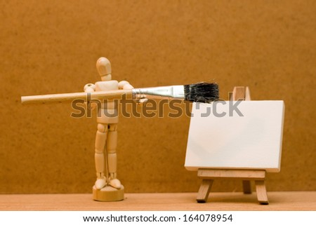 wooden manikin with large paint brush and easel.