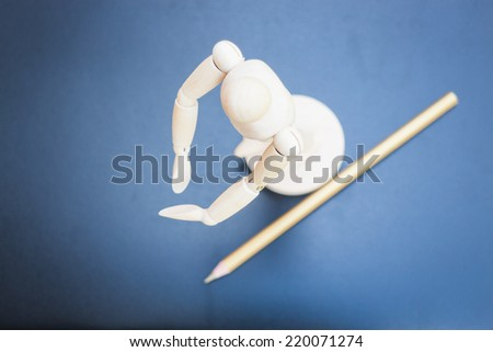 Wooden mannequin and pencil on dark background, stock photo - stock photo