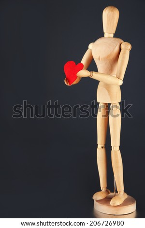 Wooden mannequin holding red heart on gray background - stock photo