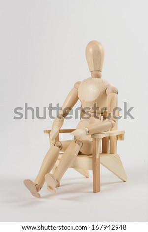 Wooden mannequin sitting in a lawn chair. - stock photo