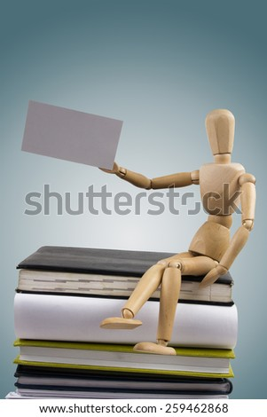 Wooden mannequin sitting on stack of books holding white business card. - stock photo