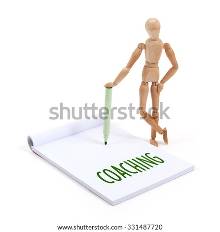 Wooden mannequin writing in a scrapbook - Coaching - stock photo