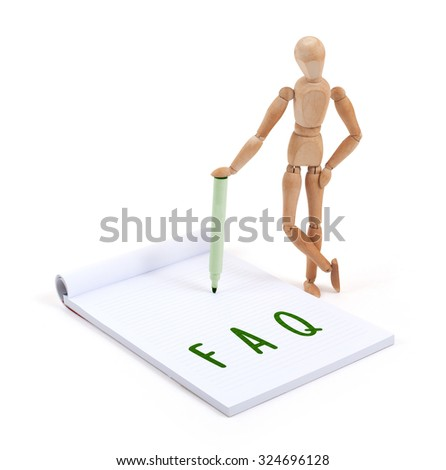 Wooden mannequin writing in a scrapbook - FAQ - stock photo