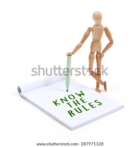 Wooden mannequin writing in a scrapbook - Know the rules - stock photo