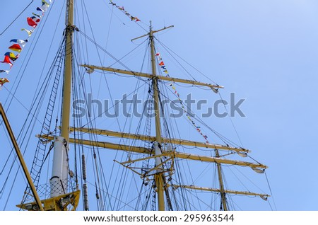 Wooden masts and rigging of a tall ship with the sails furled and colorful bunting strung across the masts against a blue sky - stock photo
