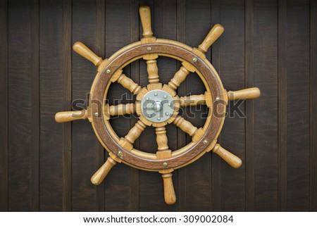 Wooden metal old wheel steering on wood background. - stock photo