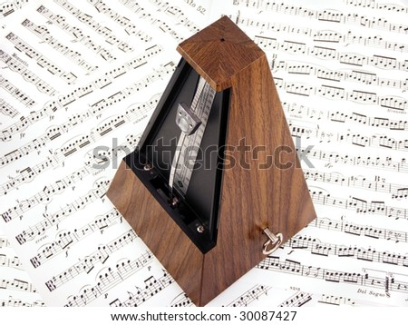 Wooden metronome on sheet music.