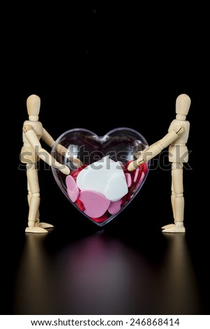 Wooden models hold heart - stock photo