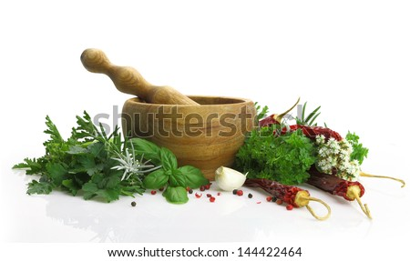 Wooden mortar and pestle with fresh herbs - stock photo