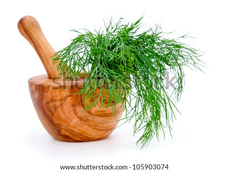wooden mortar with dill, on white background