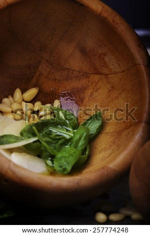Wooden mortar with pesto ingredients: fresh basil, pine nuts, parmesan cheese flakes - stock photo