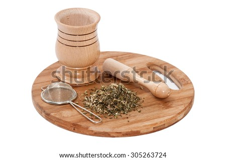 Wooden mortar with tea made from basil and metal strainer.