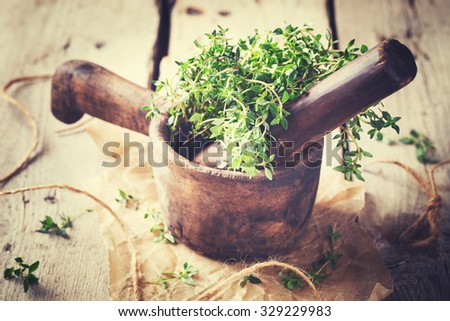 Wooden mortar with thyme. Vintage mortar made of solid wood.Toned image. Vintage style.