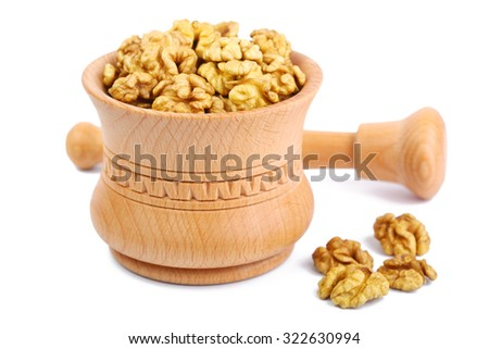 Wooden mortar with walnut kernels - stock photo
