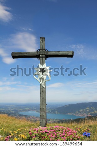 wooden mountain cross with edelweiss and alpine flowers, view to bavarian lake tegernsee , german landscape - stock photo