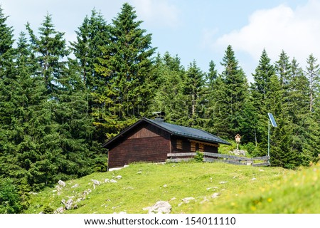 Wooden mountain refuge with solar panels and display of a holy figure in the Bavarian Alps - stock photo