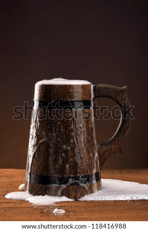 Wooden mug of fresh beer on dark red background. - stock photo