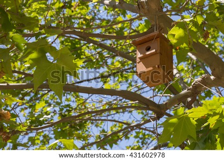 Wooden nesting box hanging on the tree - stock photo