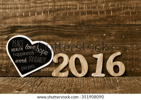 wooden numbers forming the number 2016 and a heart-shaped chalkboard with some wishes for the new year, such as peace, love and happiness, on a rustic wooden surface - stock photo