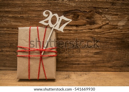 wooden numbers 2017 happy new year with gift box and red ribbon on wooden brown background. empty copy space for inscription.