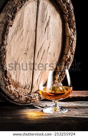 Wooden oak barrel and a glass of cognac - stock photo