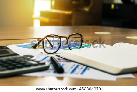 wooden office desk with open diary book and data chart,business concept